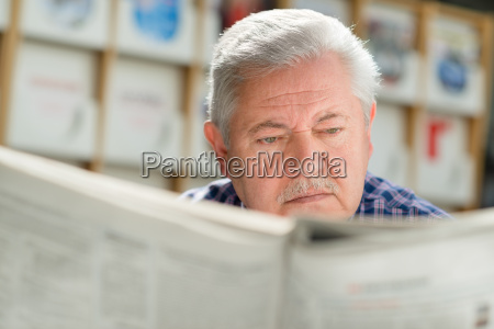 elderly man with mustache reading paper