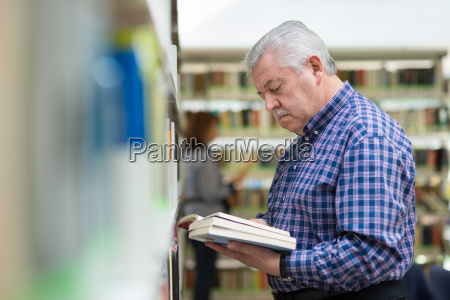 old man reading and choosing book