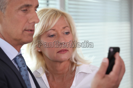 man showing mobile phone to woman