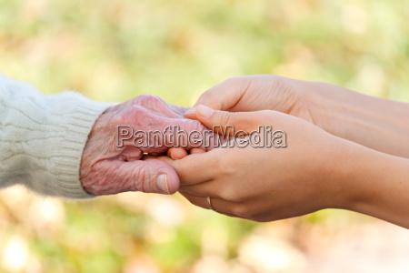 senioren und junge haende halten
