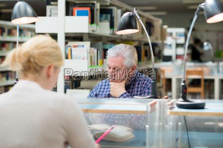 senior man studying among young people