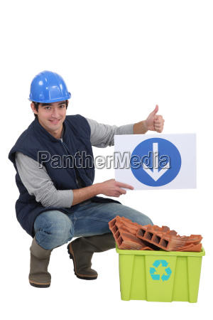 tradesman holding a sign pointing to