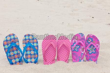 three pairs flipflops on sandy beach