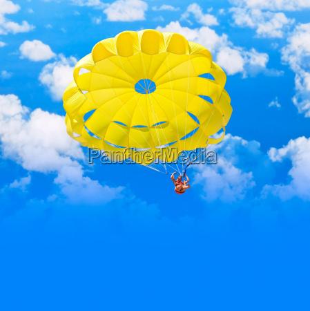 weiblicher fallschirmspringer ueber blauem sommerhimmel