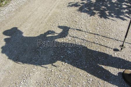 silhouette eines bergwanderers auf schotterstrasse