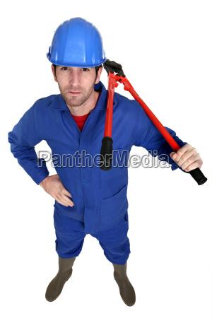 man carrying bolt cutter over shoulder