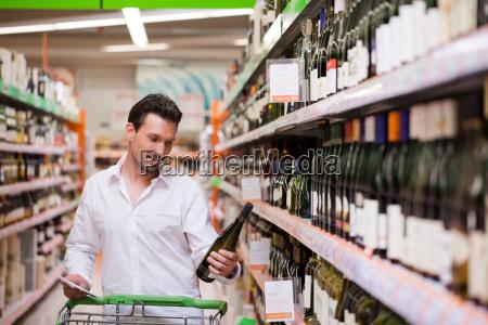 junger mann sucht nach einer flasche