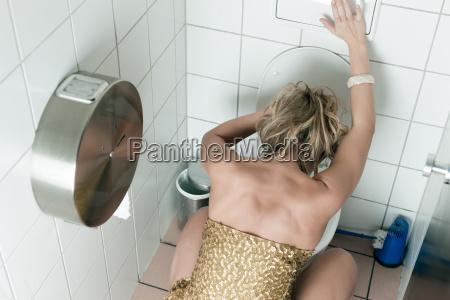 frau uebergibt sich in der toilette