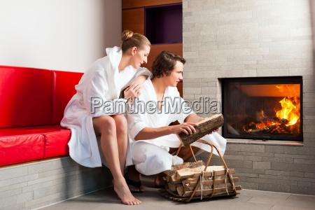 junges paar sitzt im bademantel vor