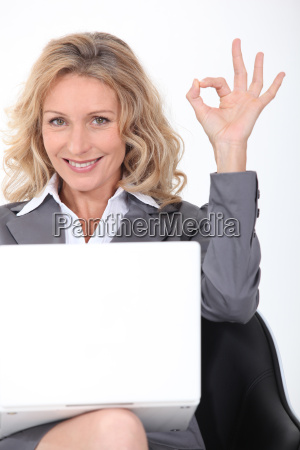 blonde businesswoman with a laptop giving