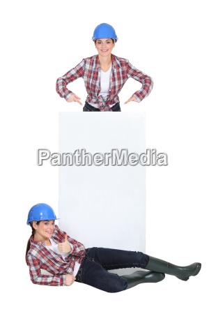tradeswomen standing around a blank sign