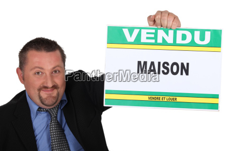 estate agent holding a vendu sign