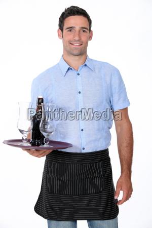 kellner mit schale und flasche bier