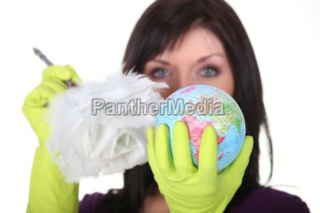 eine charwoman die einen globus reinigt