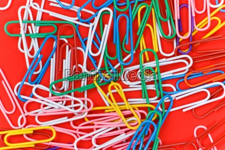 many colourful paper clips on red