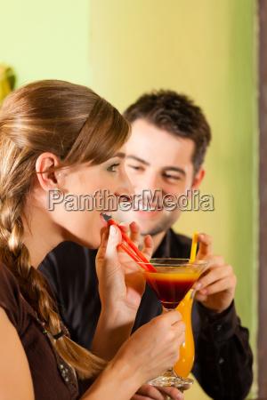 junges paar trinkt cocktails in einer
