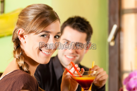 young couple drinks cocktails in a