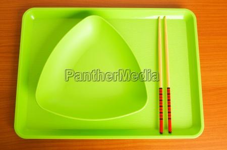 asiatisches nahrungsmittelkonzept mit platte und essstaebchen