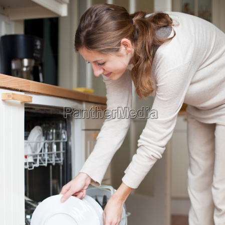 housework young woman putting dishes in