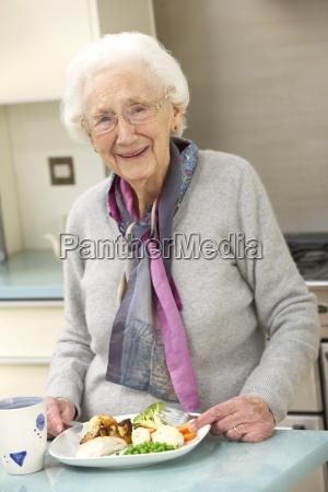 senior woman enjoying meal in kitchen