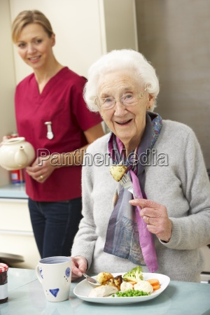 senior woman with carer eating meal