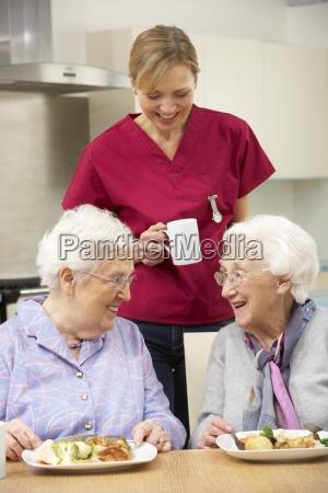 senior women with carer enjoying meal