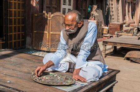 alter inder sitzen sortiert knoepfe und