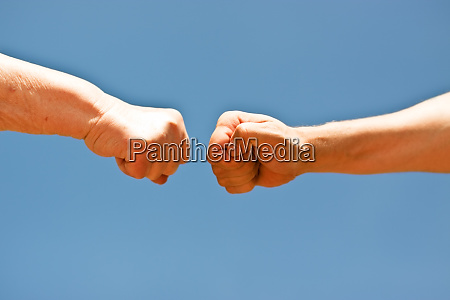 two fists in front of blue