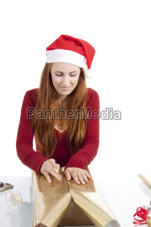 young woman packs gifts for christmas