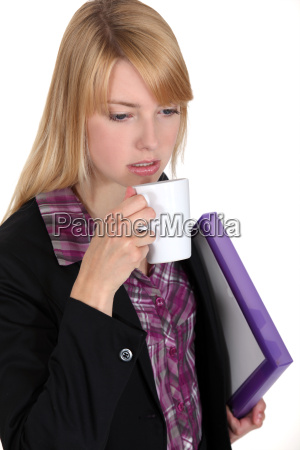 woman with coffee cup and folder