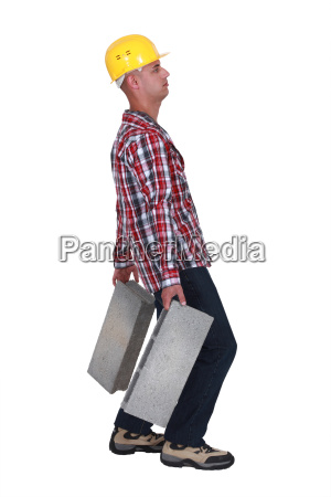 man carrying two heavy building blocks