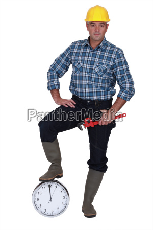 builder resting foot on clock