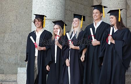 smiling absolventen posiert waehrend ihr diplom