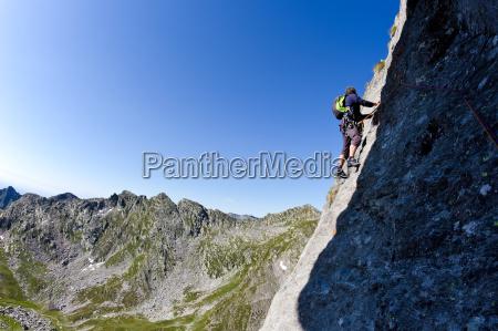 caucasian male climber climbing a steep