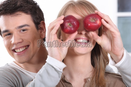 young man holding red apples before