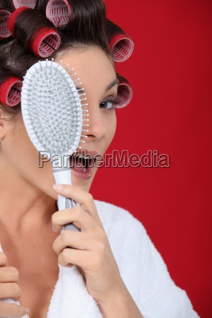 woman with hair curlers holding a