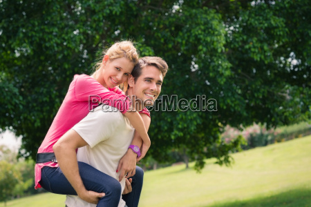 young couple running piggyback in city