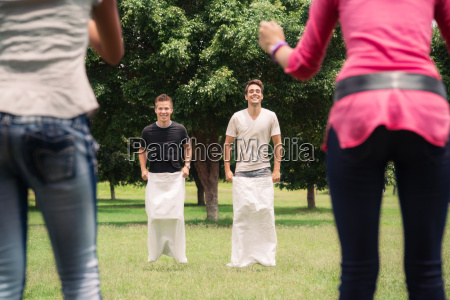 men playing sack race with girlfriends