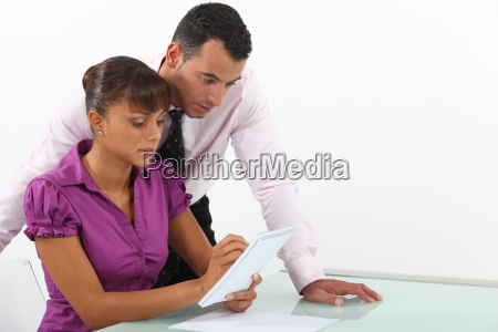 two businesspeople writing down ideas
