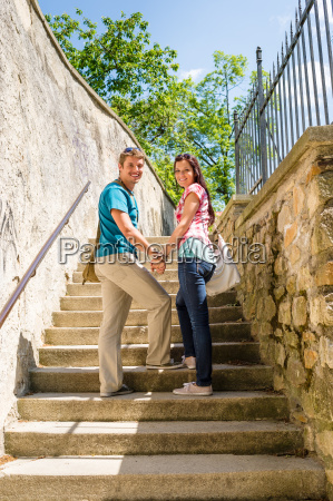 young couple smiling holding hands on