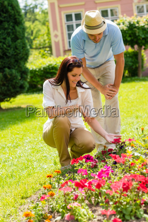 young couple look flowers in sunny
