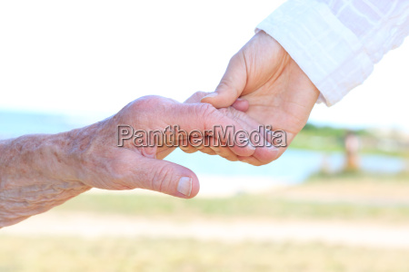 young and senior women holding hands