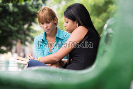 college students studying on textbook in