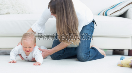 mother catching a baby in living