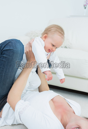 mother lying while holding a baby