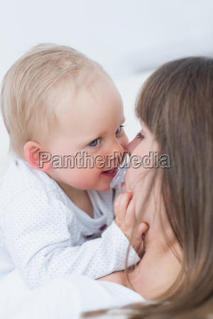 baby catching a pacifier in living