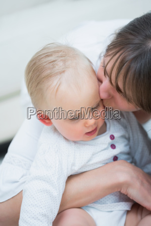 mother kissing a baby in living