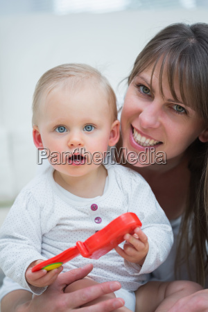 baby holding a toy in living