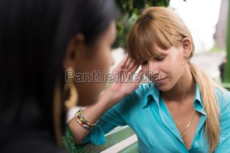 woman having headache while talking with