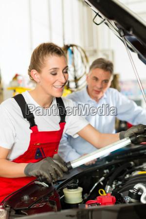 AElterer mann und junge mechanikerin am